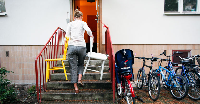 A woman carries chairs, one in each hand, up a stair to a front door.